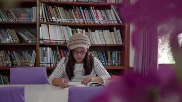 mulher sentada na frente das estantes e lendo o livro.