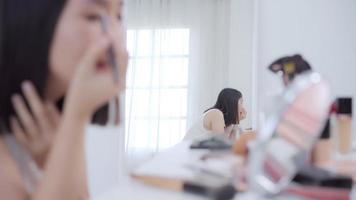 blogger de belleza presenta cosméticos de belleza sentados frente a la cámara frontal para grabar videos.
