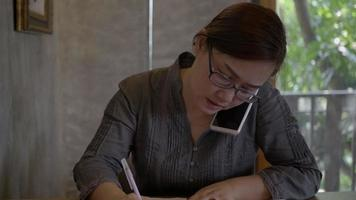 mulher usando telefone celular e escrevendo notas.