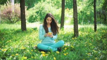 donna con il telefono che si siede sull'erba