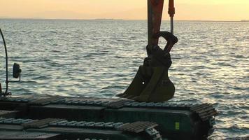excavadora trabajando junto al mar.