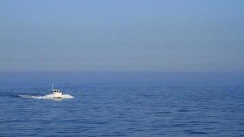 uma foto azul com um barco navegando no mar