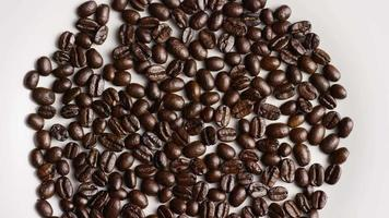 Rotating shot of delicious, roasted coffee beans on a white surface - COFFEE BEANS 027