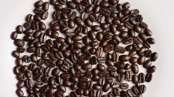colpo rotante di deliziosi chicchi di caffè tostati su una superficie bianca - chicchi di caffè 027