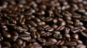 colpo rotante di deliziosi chicchi di caffè tostati su una superficie bianca - chicchi di caffè 023
