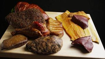 Rotating shot of a variety of delicious, premium smoked meats on a wooden cutting board - FOOD 051