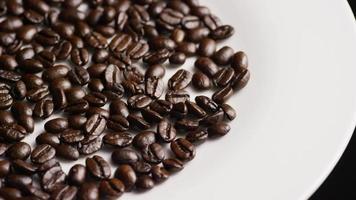 colpo rotante di deliziosi chicchi di caffè tostati su una superficie bianca - chicchi di caffè 038