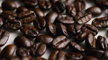colpo rotante di deliziosi chicchi di caffè tostati su una superficie bianca - chicchi di caffè 043