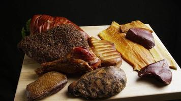 Rotating shot of a variety of delicious, premium smoked meats on a wooden cutting board - FOOD 048