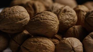 filmische, roterende opname van walnoten in hun schelpen op een wit oppervlak - walnoten 087