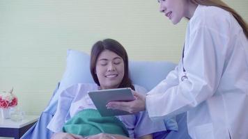 lindo inteligente médico asiático e paciente discutindo e explicando algo com o tablet nas mãos do médico. video