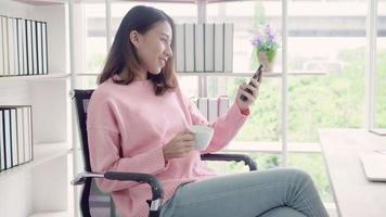 mulher asiática em desgaste casual inteligente usando smartphone e bebendo uma xícara de café quente no escritório.
