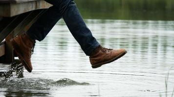 Mann, der sein Bein am See schwingt und am Rand eines Holzdocks sitzt