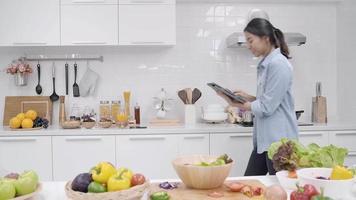 Feliz mujer asiática con tableta para receta mientras prepara comida en la cocina.
