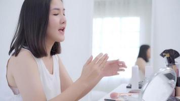 blogueira de beleza apresenta cosméticos de beleza sentados na frente da câmera para gravar vídeo. video