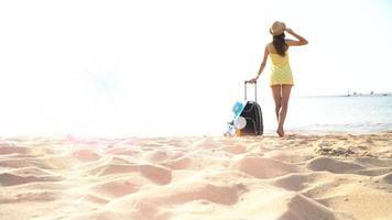 mulher na praia com uma mala