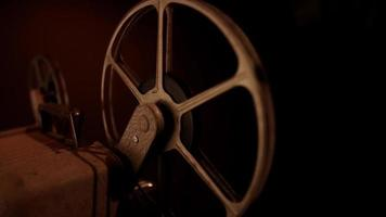 Traveling shot of rusty film reels spinning with dark illumination in 4K