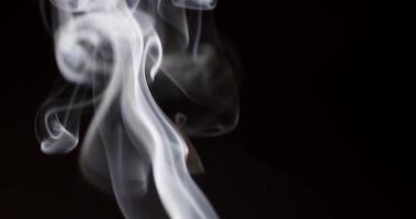 Chiuda in su di belle forme di fumo che galleggiano nell'oscurità in 4K