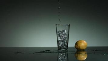 líquido transparente carbonatado vertido y salpicado en cámara ultra lenta (1,500 fps) en un vaso lleno de hielo - líquido vertido 006