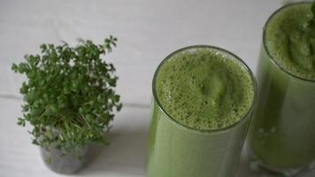 Blended green smoothie with ingredients or cocktail on white background. video