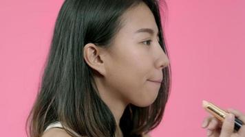 junge schöne modische asiatische Frau, die Lippenmake-up mit kosmetischem Pinsel in Freizeitkleidung anwendet.