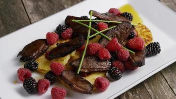 colpo rotante di un delizioso piatto di pancetta affumicata d'anatra con ananas grigliato, lamponi, more e miele - cibo 095