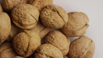 filmische, roterende opname van walnoten in hun schelp op een wit oppervlak - walnoten 054