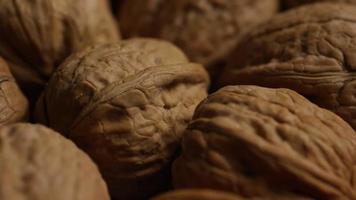 filmische, roterende opname van walnoten in hun schelpen op een wit oppervlak - walnoten 018