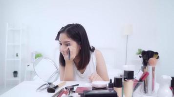 feliz linda jovem asiática usar revisão de cosméticos maquiagem tutorial transmitido vídeo ao vivo para rede social.