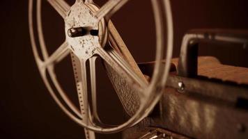 Toma estática de carrete de película girando en proyector de película con iluminación cálida en 4k video