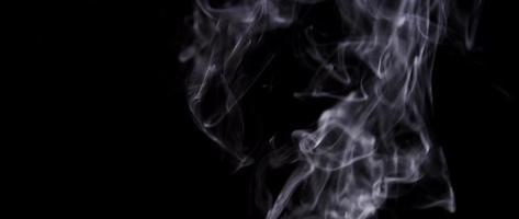 fumo bianco informe che galleggia e disegna linee curve irregolari nell'oscurità in 4K