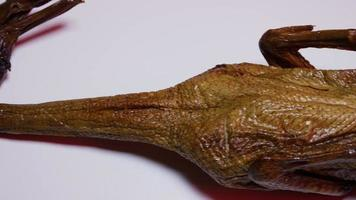 Un pato ahumado completo sobre una superficie blanca con un fondo rojo - pato ahumado 026