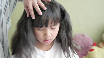 familia asiática con madre cepillando el cabello de su pequeña hija.
