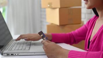 mulher digitando o número de um cartão de crédito em um laptop