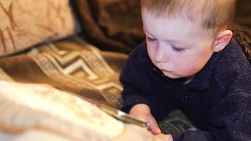 niño jugando con el teléfono móvil en el sofá