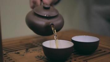 Cerrar la mano vertiendo té en dos tazas diferentes video