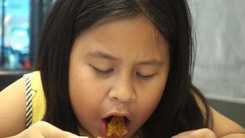 menina asiática comendo uma coxa de frango
