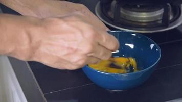 usando una cuchara para batir los huevos en una taza de cerámica.