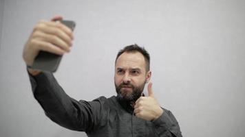 un hombre con barba hace una selfie en el teléfono video