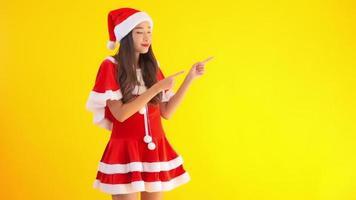 Joven asiática santa niña vistiendo gorro de navidad sobre antecedentes aislados