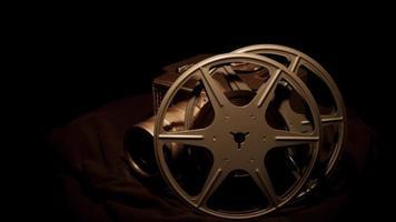 foto de alto ângulo de dois rolos de filme e uma câmera clássica girando com fundo escuro em 4k