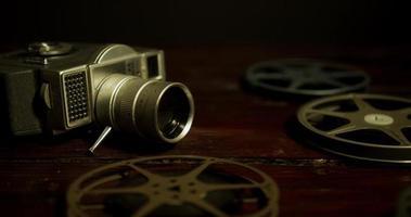 panning shot em superfície de madeira de bobinas, uma câmera e filme caindo com iluminação escura em 4k