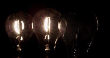 três lâmpadas clássicas brilhando na escuridão, a lâmpada em primeiro plano ligando e desligando em 4k