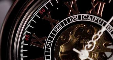 Extreme close up of pocket watch with exposed machinery coming twenty minutes in 4K time lapse video