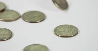 muchas monedas de un cuarto de dólar cayendo y girando sobre tres monedas en la mesa blanca, siete monedas colocadas en la escena en 4k