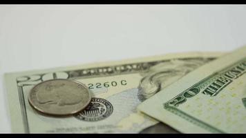 muchas monedas de un cuarto de dólar cayendo sobre una moneda y dos billetes de $ 20 en una mesa blanca, finalmente una moneda y ambos billetes colocados en la escena en 4k