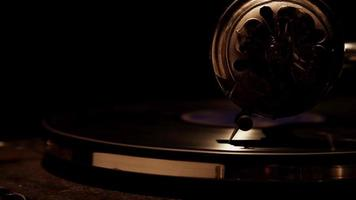 Dark extreme close up of decorated needle playing a vinyl disc on classic record player and weak overhead lighting in 4K