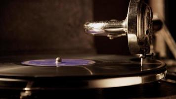 Dark scene of static medium shot of record player with vinyl disc illuminated from left side creating hards shadows in 4K