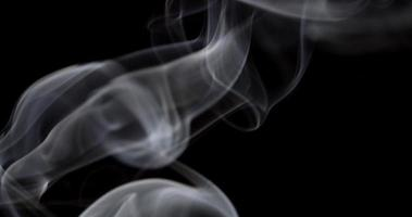 Soft controlled smoke in studio floating and drawing spirals, swirls and waves in darkness in 4K video