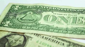 Homme mettant une tour de pièces sur deux billets d'un dollar